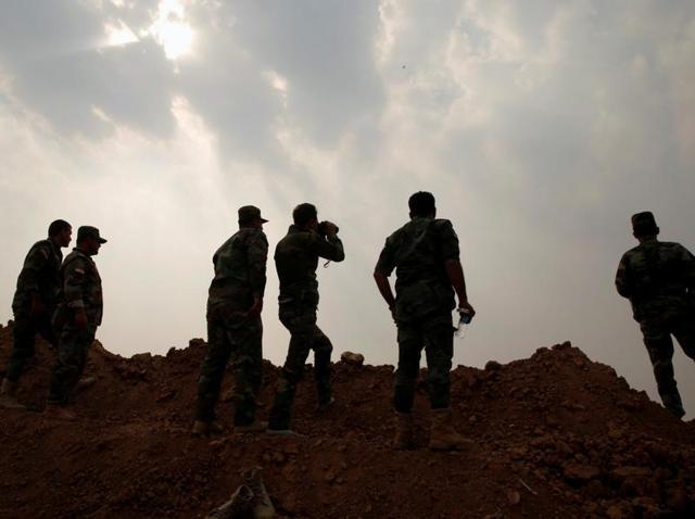 Kurdish peshmerga fighters observe the battle between the Iraqi army and Islamic State militants at Topzawa village, near Bashiqa, near Mosul, Iraq.