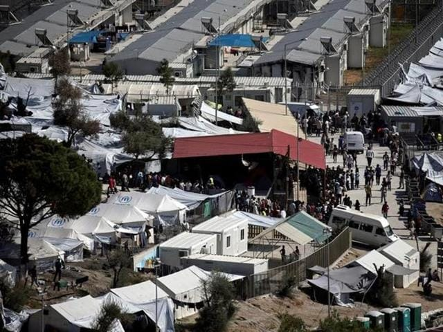 Refugees and migrants line up for food distribution at the Moria migrant camp on the island of Lesbos, Greece.