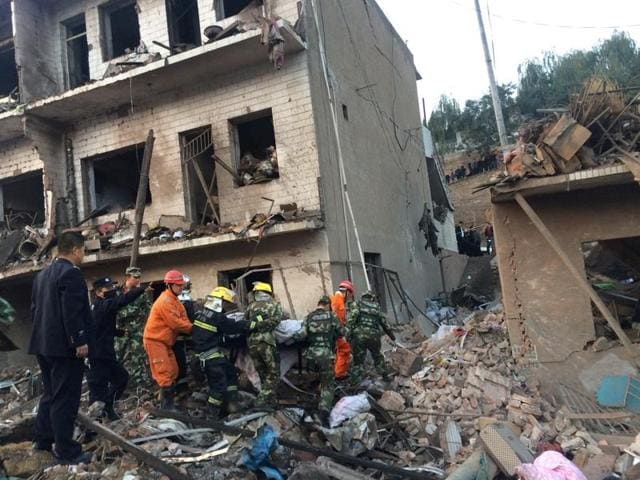 Rescue workers search at site after an explosion hit a town in Fugu county, Shaanxi province, China.