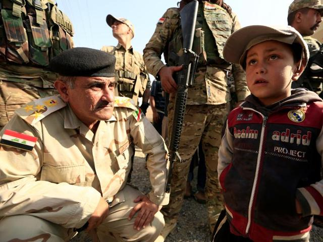 A boy whose village was taken by Iraqi army from Islamic State talks to soldiers beside his house at the town of Harrarah near Mosul, Iraq.
