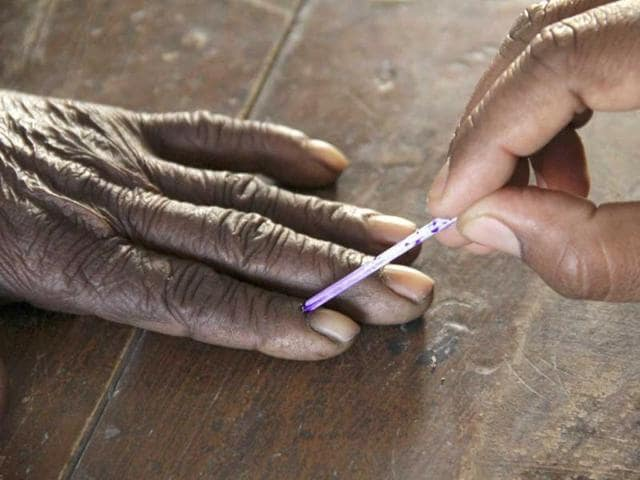 A voting official marks the finger of a voter inside a polling booth, in Azamgarh, Uttar Pradesh.