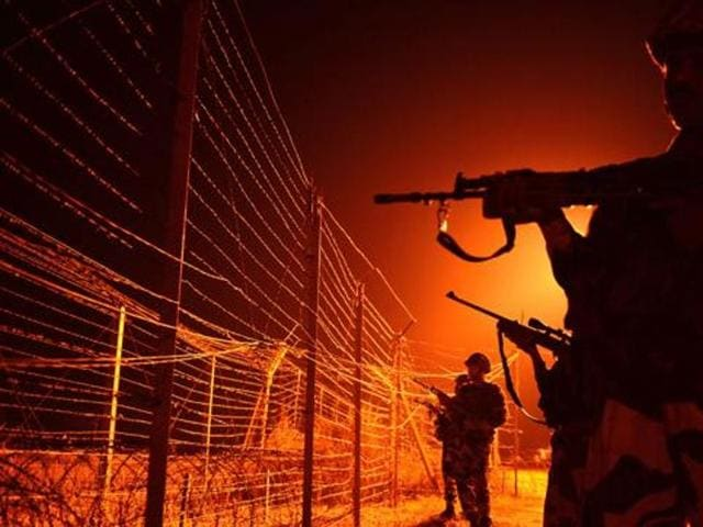 In this file photo, BSF soldiers patrol along a border fence at an outpost along the LoC between India-Pakistan at Abdulian, some 38 kms southwest of Jammu.