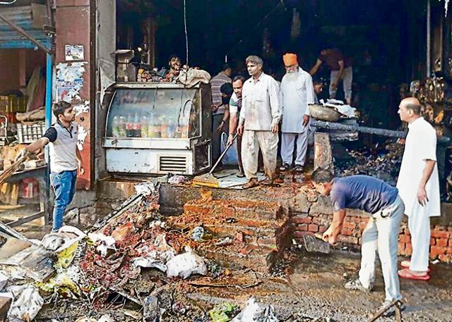 People gathering the charred remains after the fire at a grocery store in Tarn Taran on Monday.
