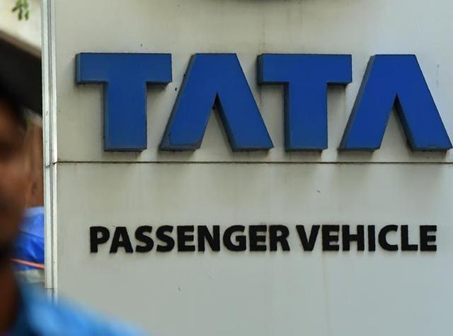 A man walks past a signage of a Tata Motor's showroom in Mumbai.