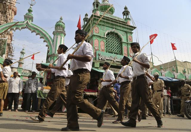 Members of Hindu nationalist Rashtriya Swayamsevak Sangh (RSS), or National Volunteer Organization, wearing the organization's new uniform, march in front of a mosque during a Vijayadashami program in Bangalore.