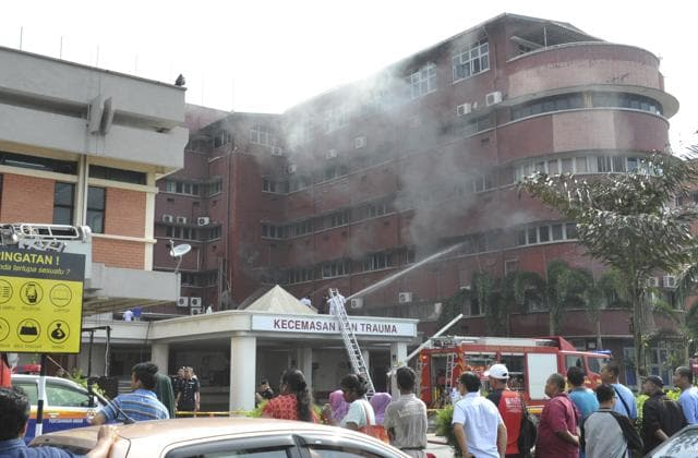 People watch firefighters putting out fire which broke out on the second floor of the Intensive Care Unit (ICU) of Hospital Sultanah Aminah in Johor Bahru in southern state of Johor, Malaysia on Tuesday.