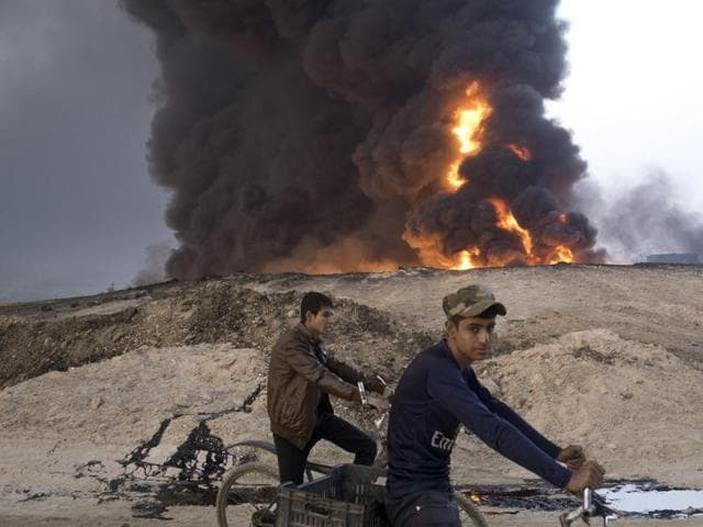 Youths ride bicycles next to a burning oil well in Qayara, about 50 km south of Mosul, Iraq. The IS group has launched diversionary attacks to prevent Iraqi forces from retaking Mosul.