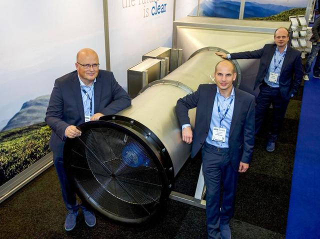 A handout photo released by tech start-up Envinity Group shows (from L) the group's Managing Partners Peter van Wees, Simon van der Burg and Tim Petter posing next to a system created by van Wees to filter fine and ultra-fine particles from ambient air at the Offshore Energy 2016 Exhibition & Conference in Amsterdam on October 25, 2016.