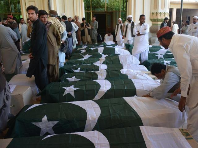 Pakistani mourners gather around the coffins of some of those killed in an attack on the Police Training College Balochistan in Quetta.