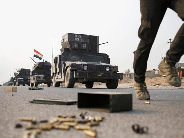 An Iraqi special forces soldier runs as other drive in armoured vehicles on a road near Mosul, Iraq.