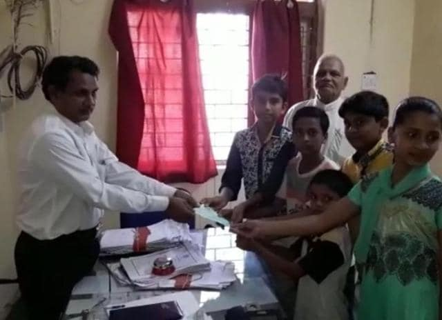 Children from Ranapur village pose with a demand draft of Rs 1,100 that they donated towards Indian Army.(HT Photo)