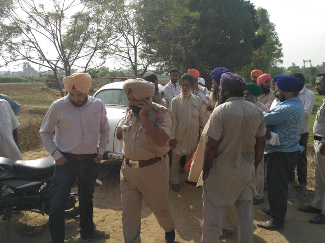 Gurkaran Singh SDO, PPCB (pink-shirt) and ASI, Amrik Singh being detained by farmers in Fatehpur village on Thursday.(HT Photo)