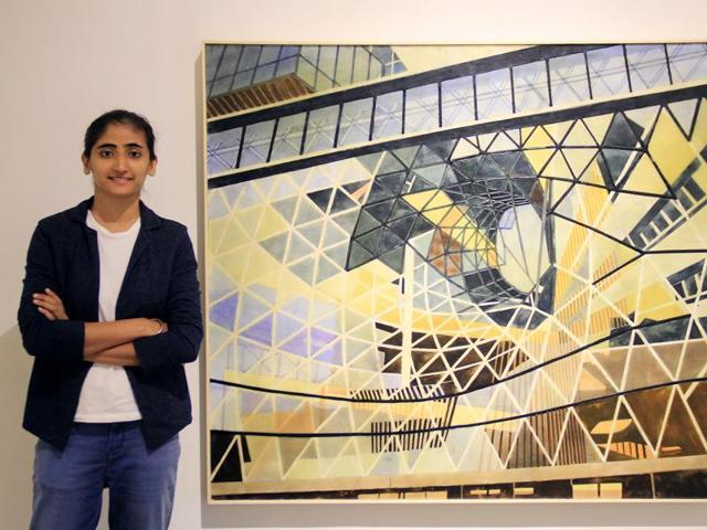 Artist Bhagyashree Suthar poses next to an untitled artwork made using beeswax on paper at Akara Art Gallery