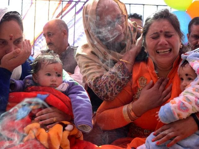 Anjana Thakur (right) in tears before handing over the boy she raised for five months to his biological mother, Sheetal Thakur (left), who holds the baby girl she returned, during a 'havan (religious ceremony)' in Shimla on Wednesday.