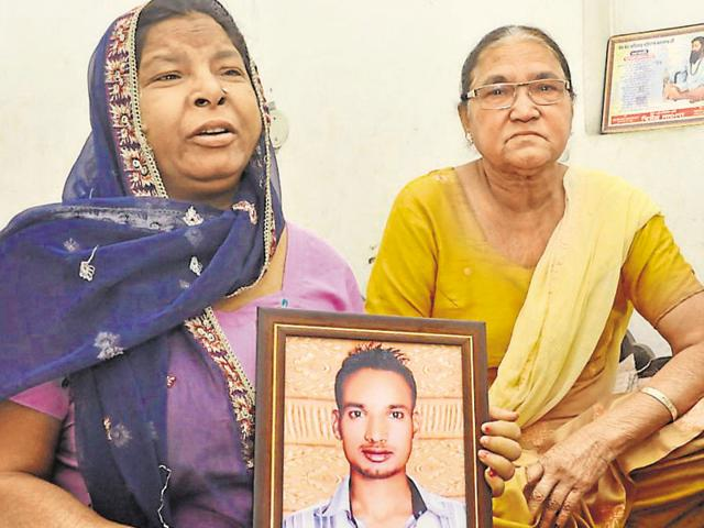 The mother of accident victim Sarbjit Singh holding his picture at her residence in Jalandhar on Thursday.