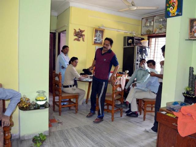 Lokayukta officials interrogate Indore zoo in-charge Dr Uttam Yadav (in red clothes) at his residence on Thursday.