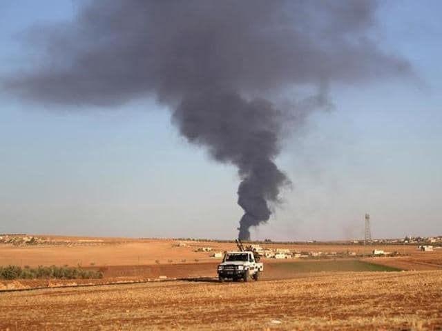 Rebel fighters ride a military vehicle near rising smoke from al-Bab city, northern Aleppo province, Syria on  October 26.