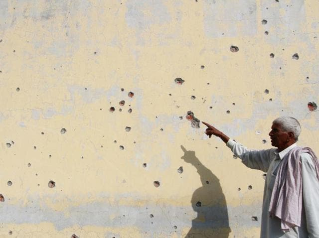 A civilian showing mortar shell marks on a wall firing from the Pakistani side of the border, at Abdullian village in RS Pura.