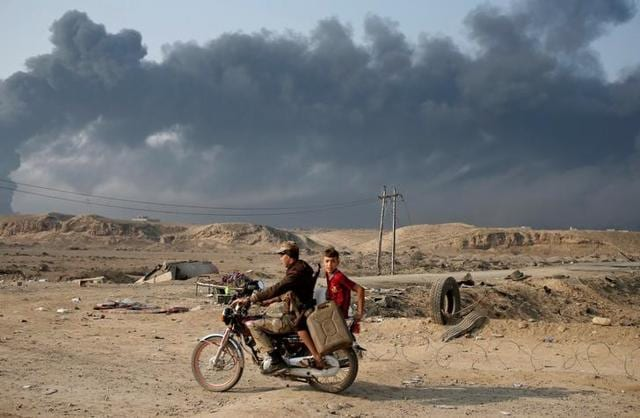 Armed members of Shi'ite militia Hashid Shaabi ride a motorbike near Qayyara, south of Mosul, Iraq. Smoke in the background is from burning oilfields set ablazed by Islamic State fighters.