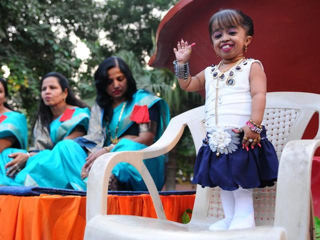 Jyoti Amge, world's shortest woman alive, stands in front of one of the largest earthen lamp of the region during a Diwali function at Jain Temple in Sector 27 on Friday.
