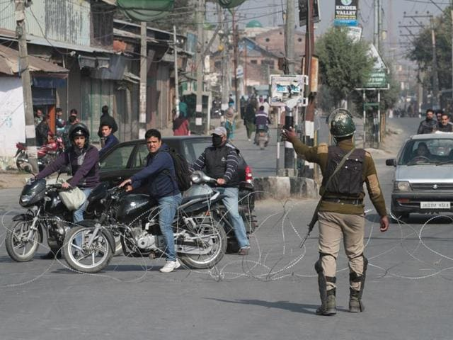 A paramilitary soldier stop people near a razor wire set up as a barricade during restrictions in Srinagar, on Thursday.(Waseem Andrabi/ HT Photo)