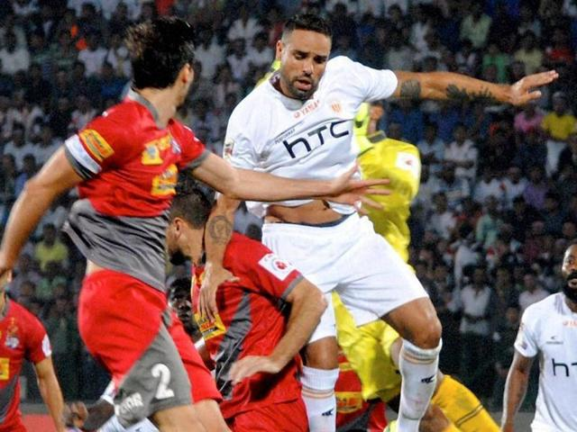 Players of Northeast United FC (in white jersey) and Atletico de Kolkata (in red jersey) vie for the ball.