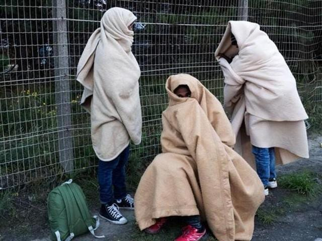 Migrants, who say they are minors, use blankets to protect themselves from the cold on a street after the dismantlement of the 'Jungle' camp in Calais, France.
