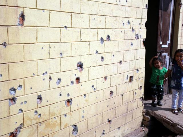 Children stand near the pockmarked wall of a building damaged by alleged shelling from the Pakistani side at RS Pura, in Jammu, on Thursday, October 27, 2016.