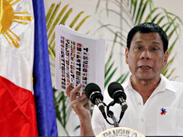 Philippine President Rodrigo Duterte shows the list of government, military and police officials involved in illegal drug trade during a news conference.