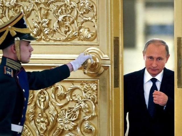 An honor guard opens the door as Russian President Vladimir Putin (R) enters a hall to attend a meeting with members of the Presidential Council for Civil Society and Human Rights at the Kremlin in Moscow.