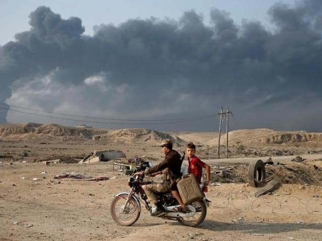 Armed members of a Shia militia Hashid Shaabi ride a motorbike near Qayyara, south of Mosul, Iraq.