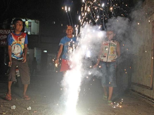 Children burn fire cracker at Dadar in Mumbai, on Friday.