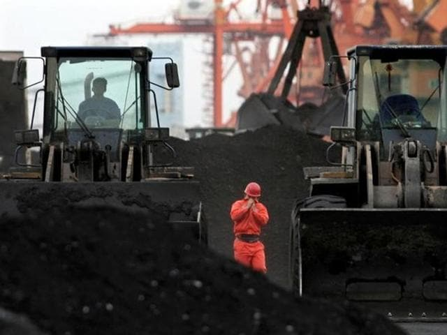 An employee walks between front-end loaders which are used to move coal imported from North Korea at Dandong port in the Chinese border city of Dandong, Liaoning province.
