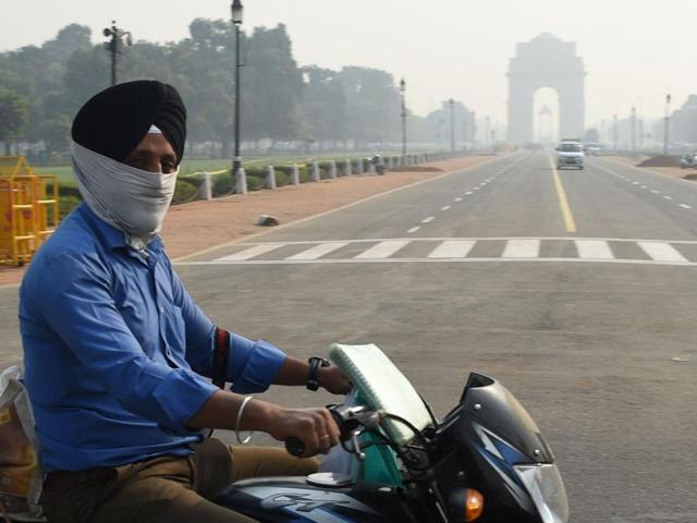A biker wearing face protection against air pollution rides in heavy smog, in New Delhi.