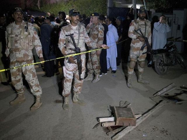 Paramilitary soldiers gather at the site of firing incident in Karachi, Pakistan.