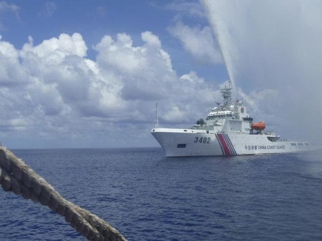 Chinese Coast Guard members approach Filipino fishermen as they confront each other off Scarborough Shoal in the South China Sea.