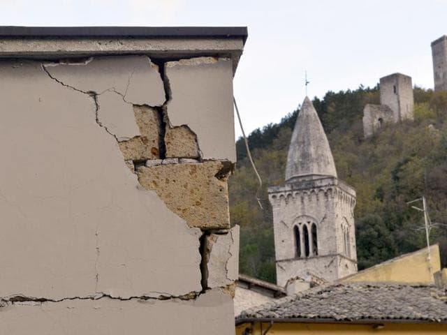 A damaged building frames more ancient towers that survived the quake in the small town of Visso in central Italy. A pair of aftershocks shook central Italy on October 26, 2016.