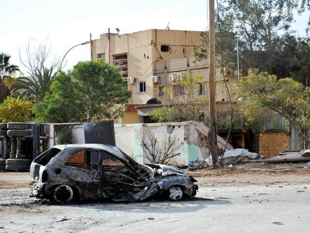 A damaged buildings and a burnt out car are seen in the Hawari area, south-west of the city of Benghazi, Libya.