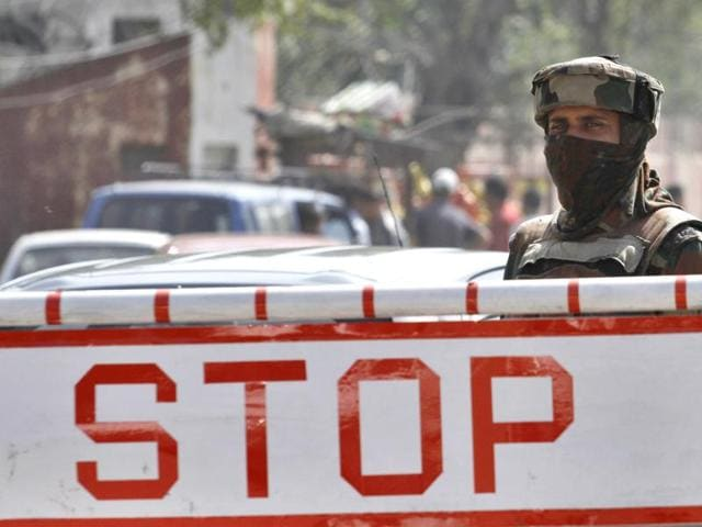 An army soldier stands guard near a check post outside Badami Bagh cantonment of the Army in Srinagar.