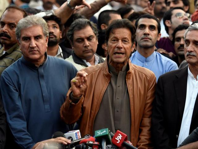Pakistani opposition leader Imran Khan (C) talks to media outside his house in Islamabad.