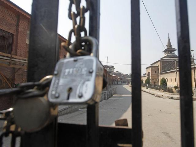 A paramilitary soldier patrols in front of the Jamia Mosque during curfew, in downtown area of Srinagar.