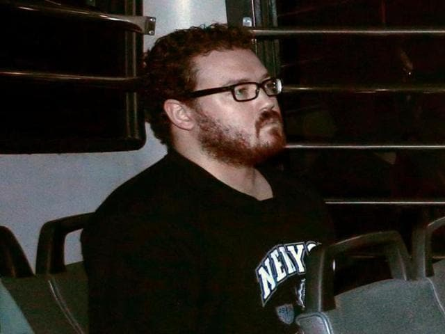 File photo of Rurik George Caton Jutting, a British banker charged with two counts of murder after police found the bodies of two women in his apartment, sitting in the back row of a prison bus as he arrives at the Eastern Law Courts in Hong Kong November 24, 2014.