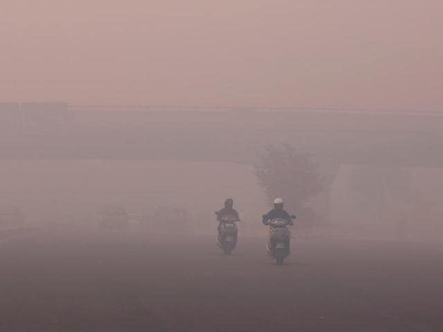 Commuters make their way amid heavy smog in New Delhi.