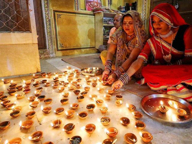 Women light earthen lamps at Ramchandran Ji temple on Diwali in Jaipur on Sunday.