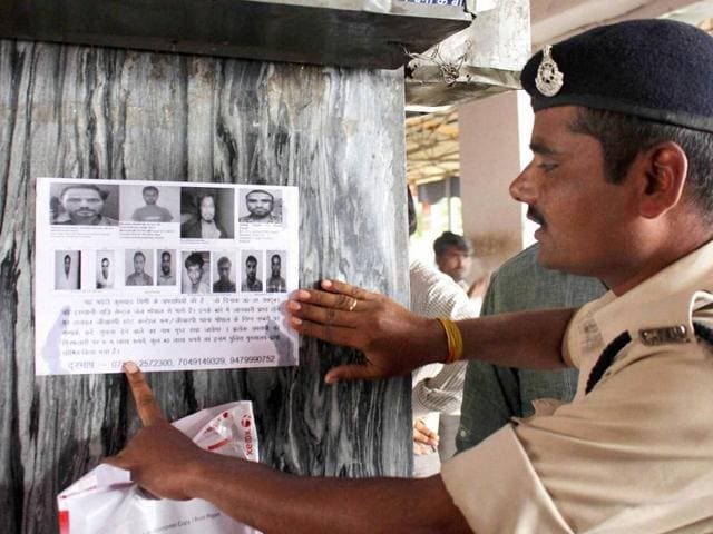 A securityman pastes wanted posters at a railway station after eight suspected SIMI members escaped from a Bhopal jail.