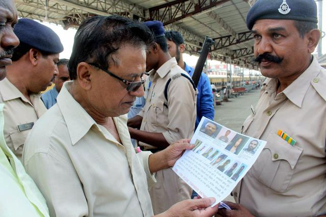 Security personnel show a wanted poster of SIMI members, who escaped from the prison, before all eight were killed in an alleged encounter.