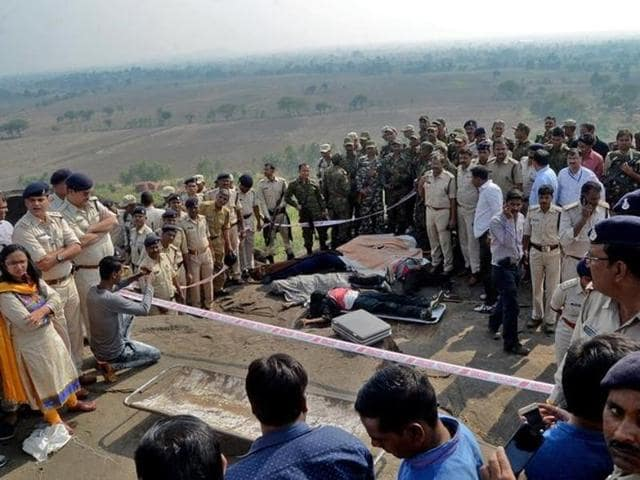 Police officers and Special Task Force soldiers stand beside dead bodies of the suspected SIMI members, who were killed in an encounter at Acharpura village on the outskirts of Bhopal, on Monday