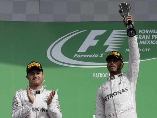 Rosberg applauds as Hamilton celebrates with his trophy.