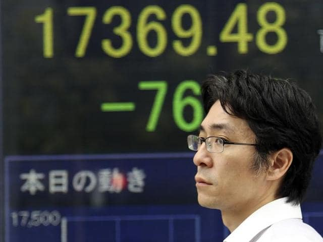 A man walks by an electronic stock board of a securities firm in Tokyo on Monday.