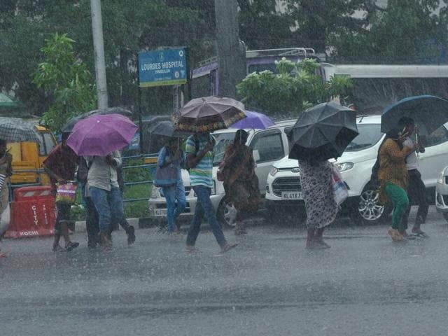 People, holding umbrellas, walk at a road during monsoon rains in Kochi.
